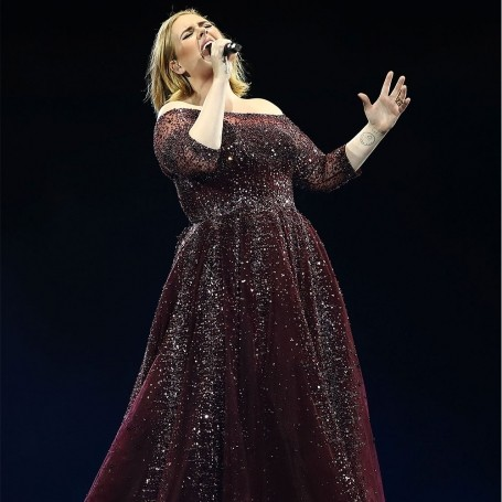 Adele performs in pouring rain rocking a poncho